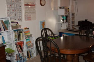 The book storage is kept in plastic milk crates on this wall. These are the books we use more frequently. The table and chairs provide a space to work together or to do crafts. You can see my teacher area in the back (it still needs some TLC).